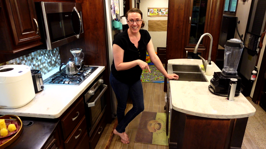 Woman pointing at RV dishwasher in the kitchen