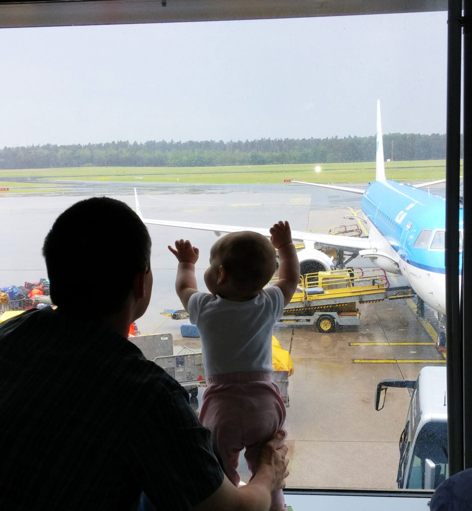 Baby waiting to travel looking out window at airplane at the gate