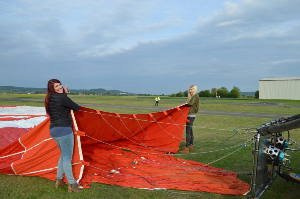 Two girls holding open the hot air balloon before it is inflated