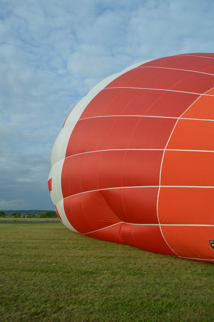 Hot air balloon partially inflated lying in a field