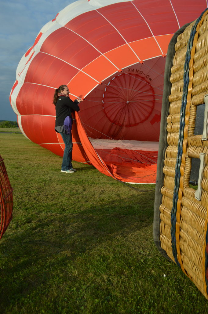 Girl holding hot air balloon open to fill with air