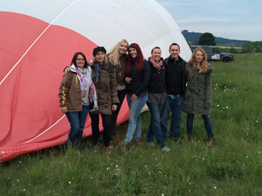 Group of passengers standing in front of the balloon after landing