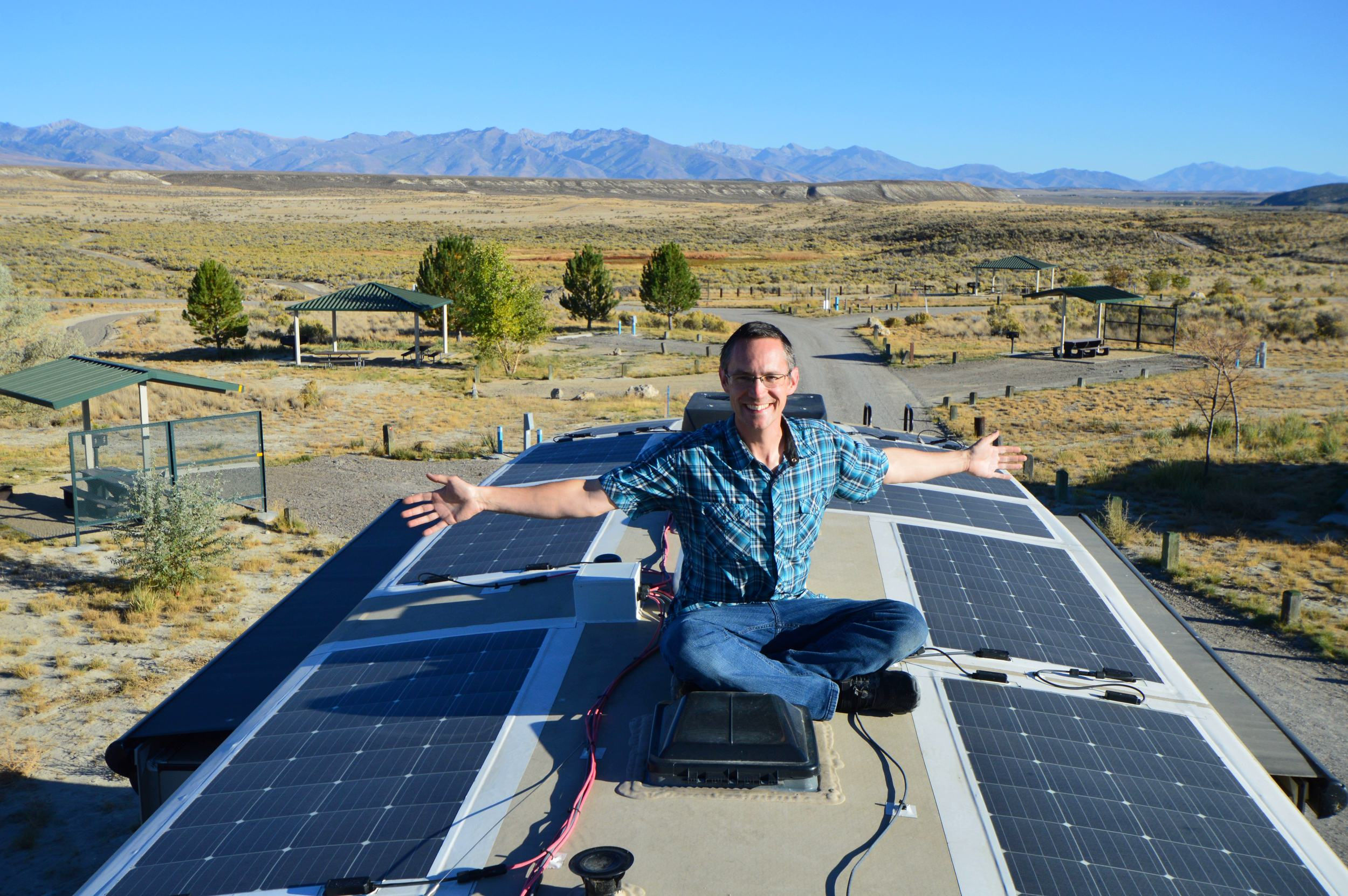 Man sitting on RV roof covered in solar panels