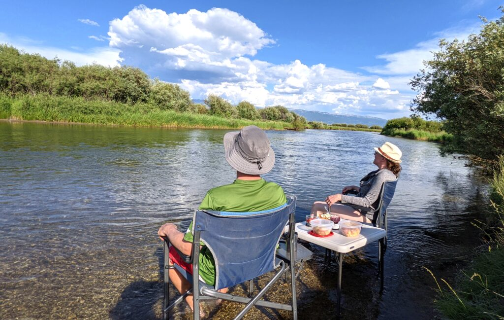 Man and woman sitting on chairs in the Teton River