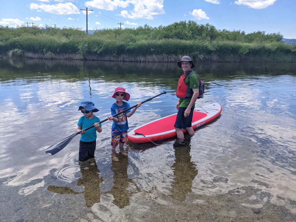 Man and kids getting paddleboard into river